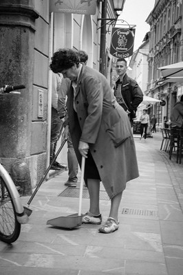 Foto på gammal kvinna som städar gata.