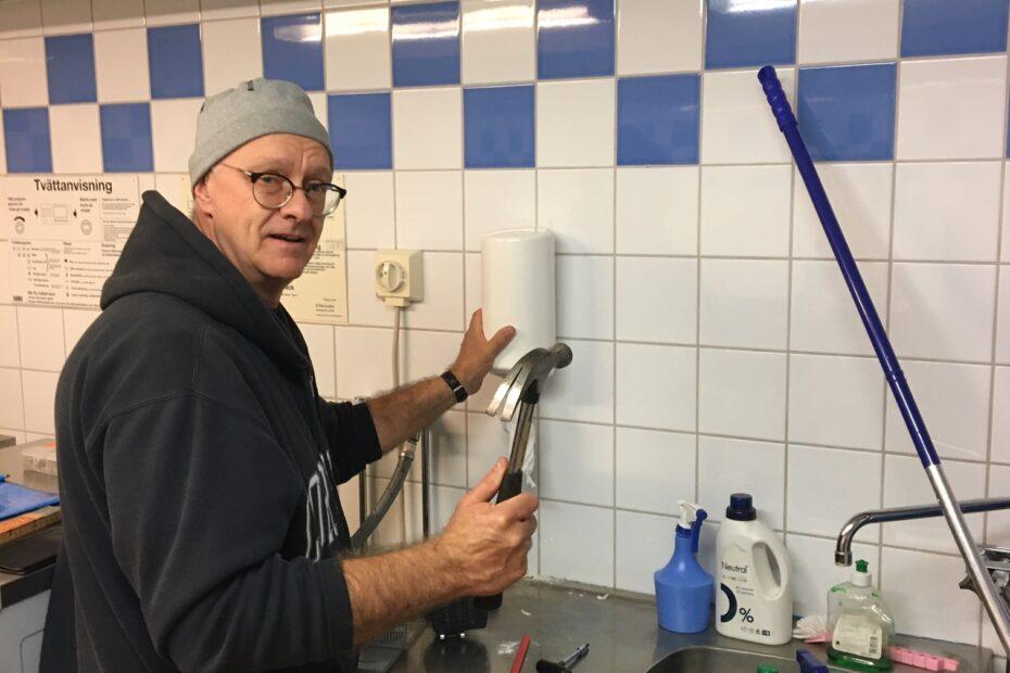Foto visar hantverkare som fixar pappershållare i tvättstugan.